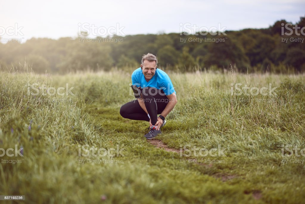 An exercising, running man clutches injured ankle stock photo