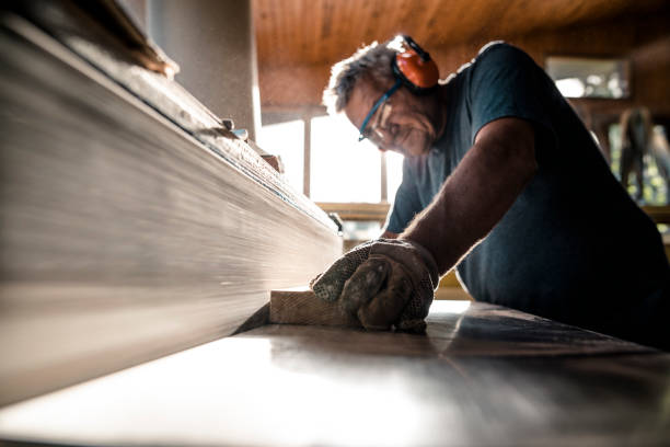 an experienced carpenter shapes the timber on a grinding wheel - logging equipment stock photos and pictures