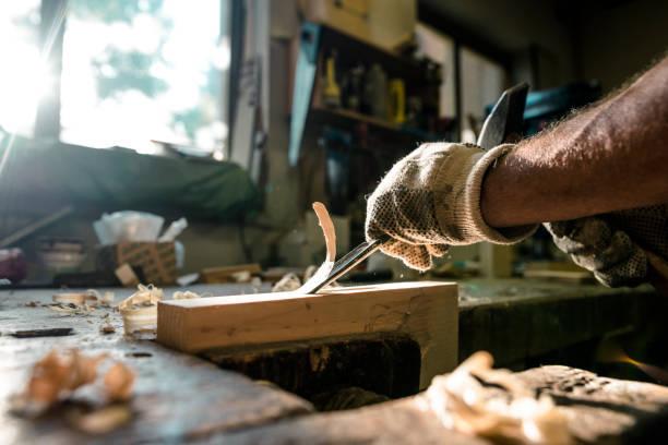 einen erfahrenen tischler formen holz mit einem meißel - schnitzmesser stock-fotos und bilder