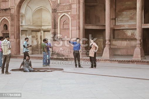 istock An expert tour guide (tourist guide) assisting a foreign visitor on vacation by providing  information on cultural, historical and contemporary heritage importance of the building. Red Fort, Delhi, India 1177843906