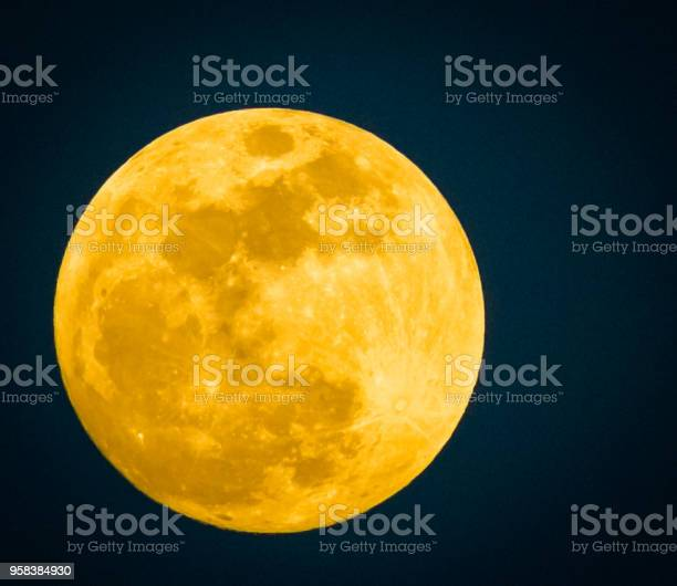 Photo of An extremely large yellowish full moon sits by itself in the night sky