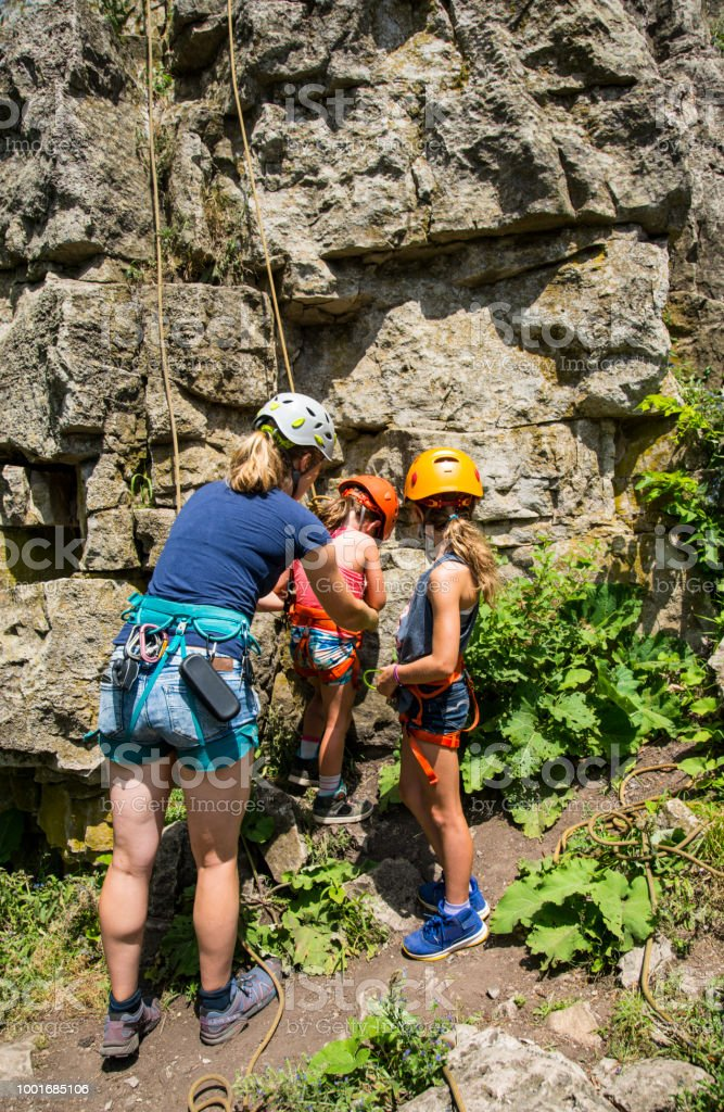 An female climbing instructor helps a young female climber outside at a rock face stock photo