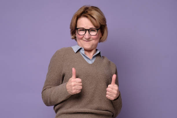 An happy senior woman showing her two thumbs up stock photo