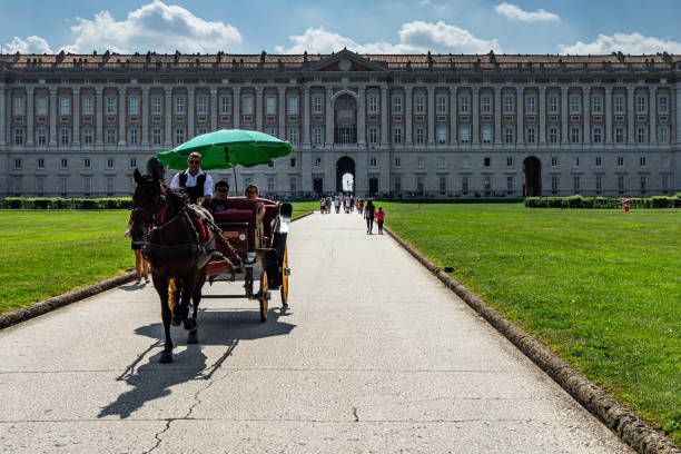 An horse carriage in front of Caserta Royal Palace riding the tourists to discover the park, Italy stock photo