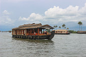 A Magnificent view of an Houseboat against the blue sky and the river in the backwaters of Alleppey in Kerala tourism / India.
