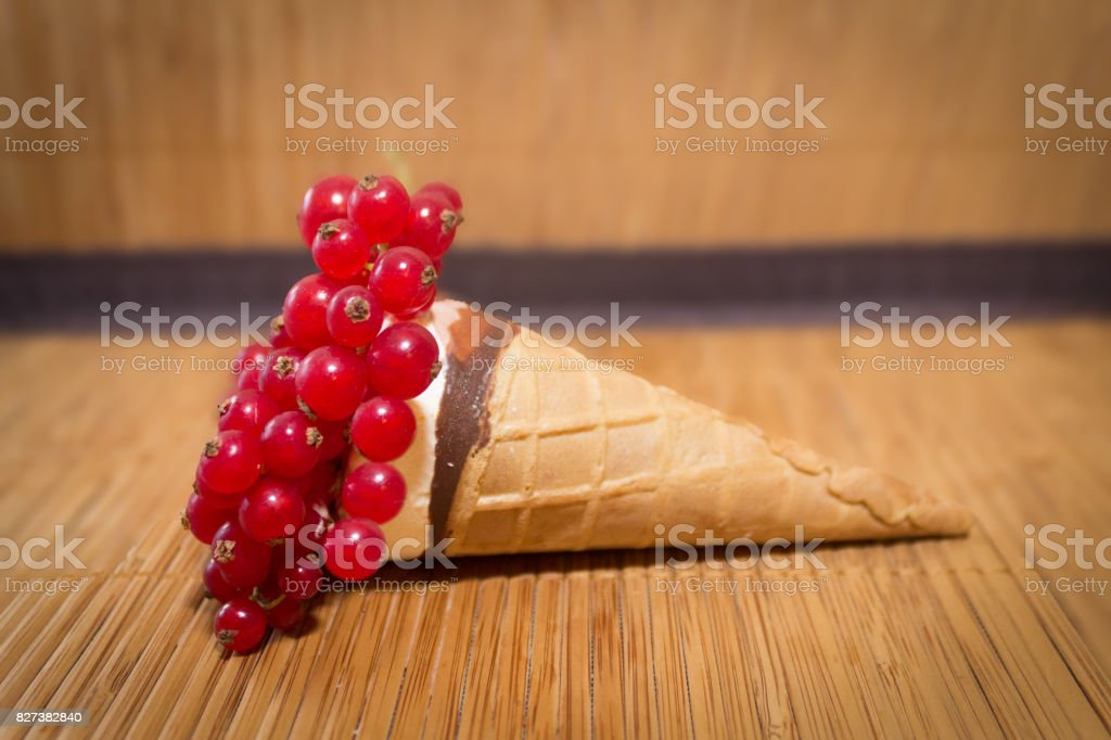 An ice cream cone with red currant stock photo
