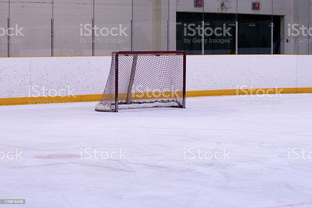 an ice rink with yellow lines on the wall and a hockey net royalty-free stock photo