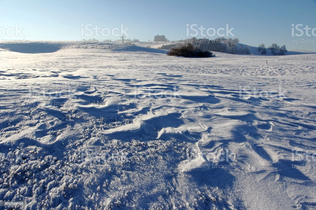 An ice-cold winter landscape with snowdrifts on a field in Bavaria stock photo