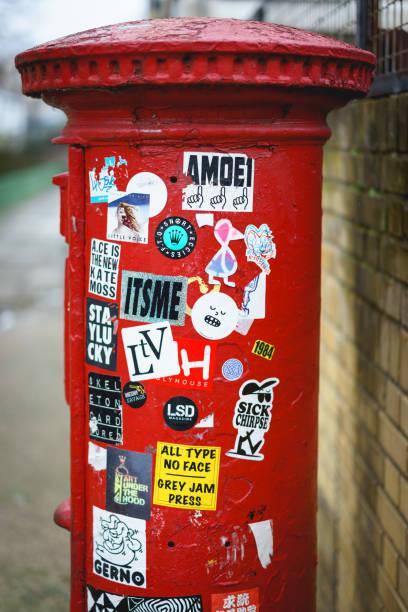 eine ikonische rote royal mail-box mit aufklebern in london (uk). - sprüche englisch stock-fotos und bilder