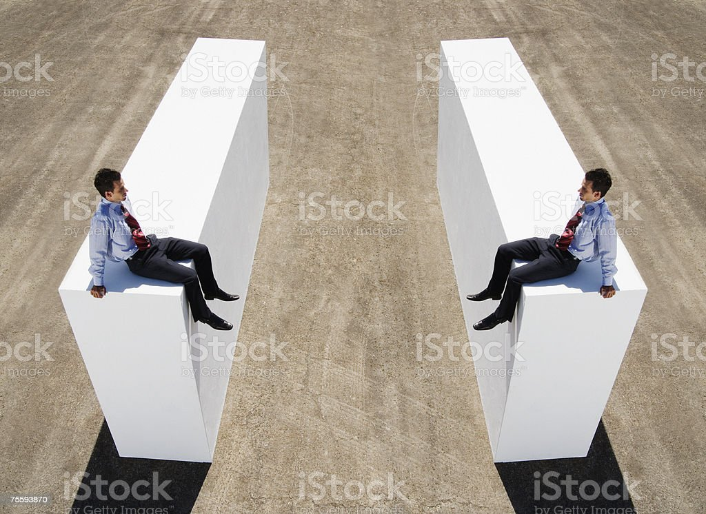 An identical split image of a businessman on a wall royalty-free stock photo