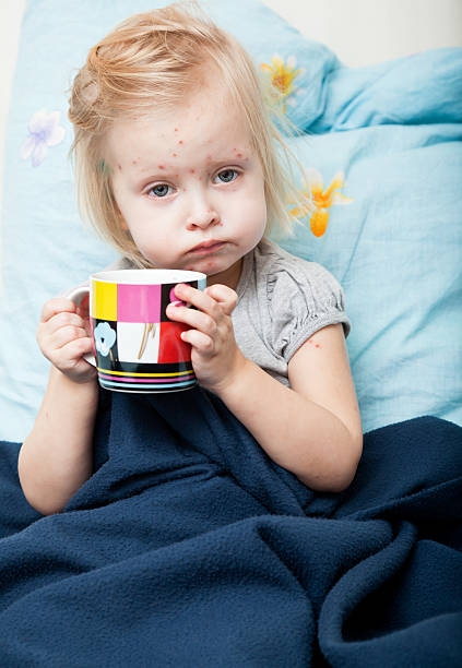 An ill girl holding a cup and sitting in bed stock photo