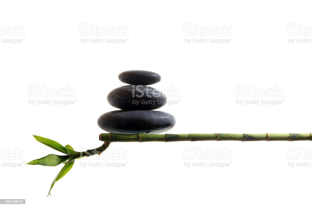 An image of 3 stacked stones balancing on bamboo stock photo