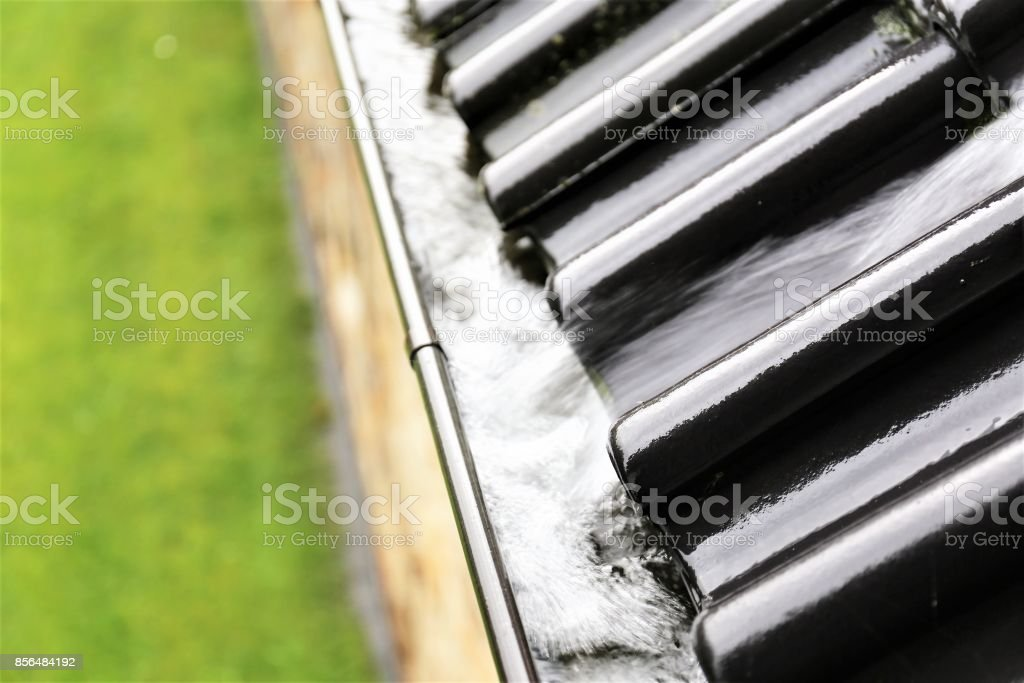 An image of a drain with raindrops stock photo