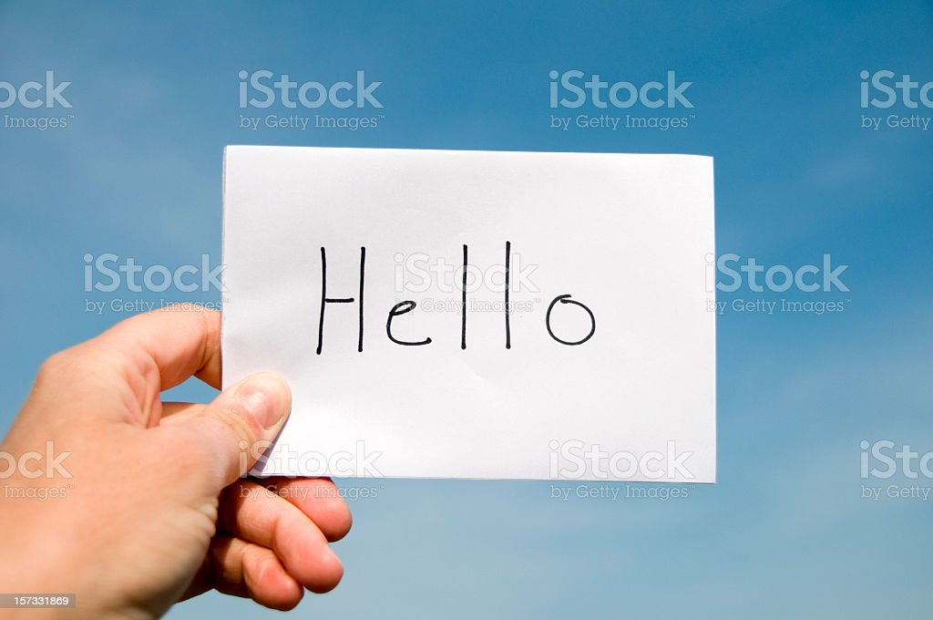 An image of a hand drawn hello sign being held up to the sky royalty-free stock photo