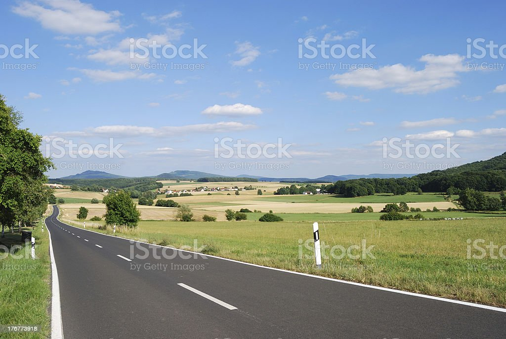 An image of a long road in the country on a sunny day royalty-free stock photo
