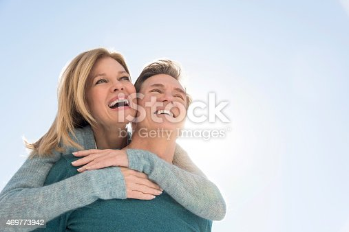 Happy couple against clear sky. Couple are in warm clothing. View is taken from below. Loving man giving piggyback ride to woman.