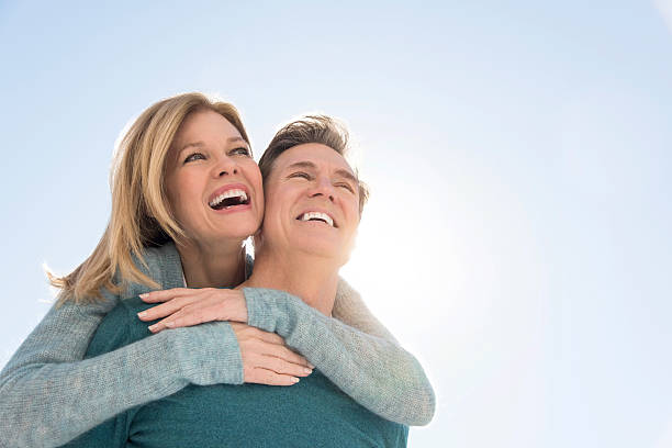 An image of a man giving a piggyback ride to a woman Happy couple against clear sky. Couple are in warm clothing. View is taken from below. Loving man giving piggyback ride to woman. mature couple stock pictures, royalty-free photos & images