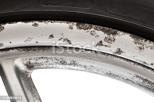 An image  of the old aluminium tyre disk with corrosion and kerb marks