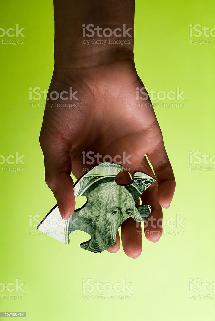 An image showing a hand holding a money puzzle game royalty-free stock photo