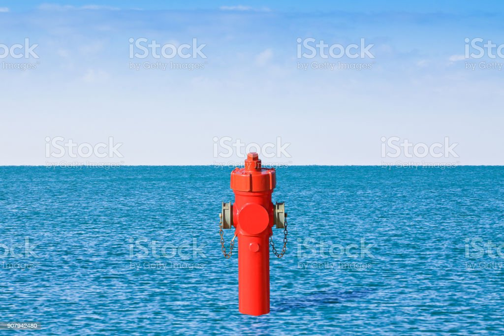 An improbable hydrant at the seaside. Plenty of water concept image stock photo