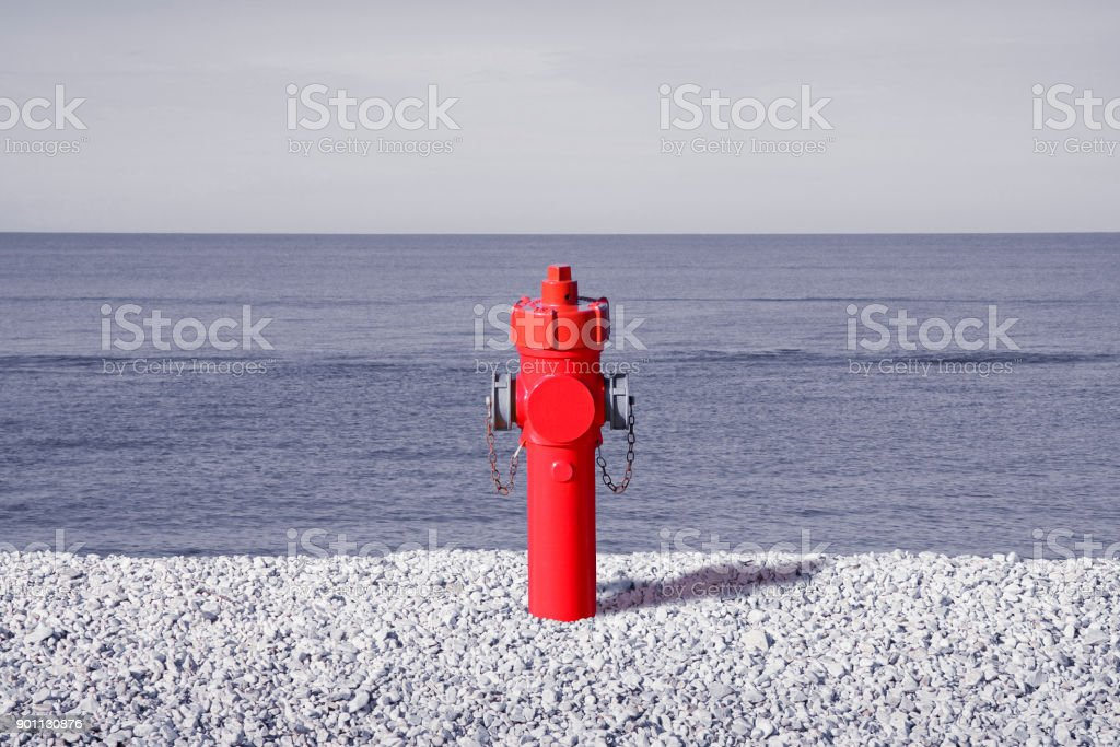 An improbable hydrant at the seaside. Plenty of water concept image'n stock photo