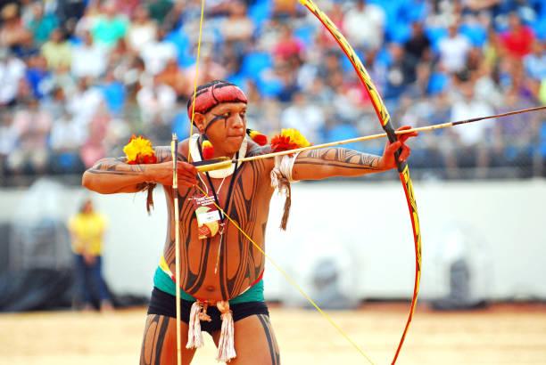 An indegenous native man from Brazil fires an arrow. stock photo