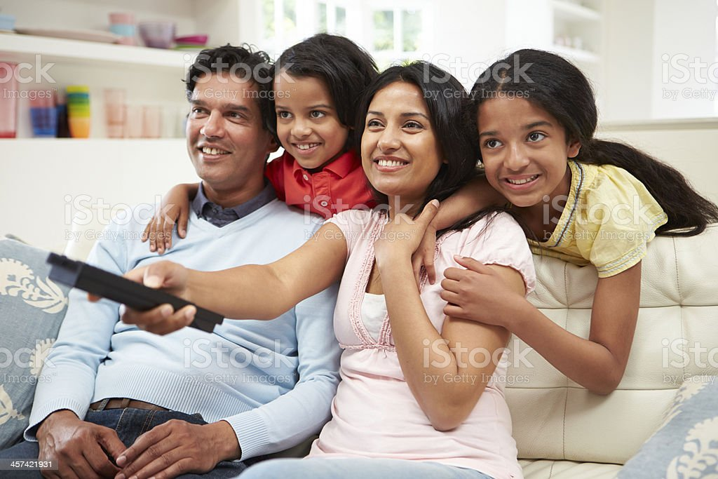 An Indian family sitting on the sofa watching television stock photo
