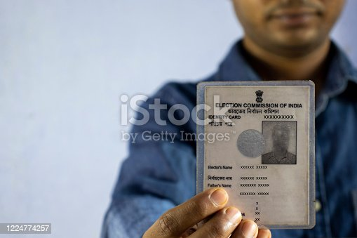 an Indian man with smiling face holding voter card on white background with selective focus or shallow depth of field