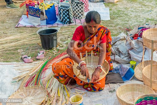 106415613istockphoto An Indian Unidentified woman preparing bamboo carving artwork of bamboo sticks items for sale in Kolkata in handicrafts trade fair. It is rural Industry in West Bengal, India on December 2019 1205199943