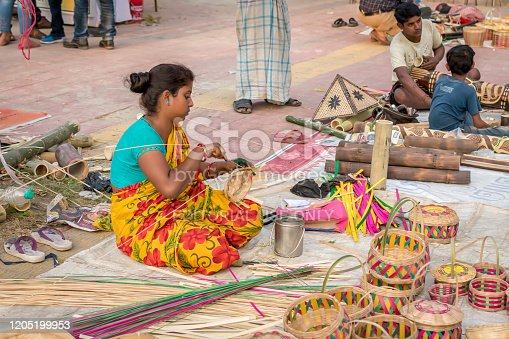 106415613istockphoto An Indian Unidentified woman preparing bamboo carving artwork of bamboo sticks items for sale in Kolkata in handicrafts trade fair. It is rural Industry in West Bengal, India on December 2019 1205199953