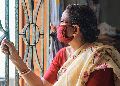 A simple looking middle aged Indian housewife looking outside from her room window during coronavirus lockdown. She is wearing a face mask. Concept of home quarantine.