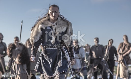 An individual female viking posing in front of a group of warriors stood in the surf on the shore