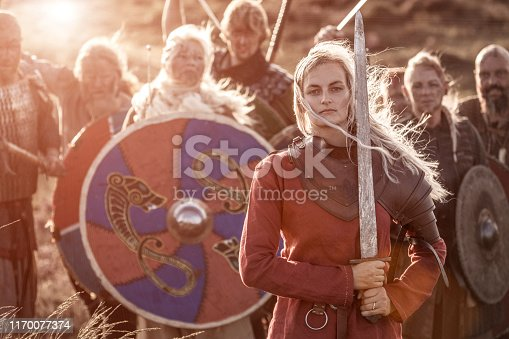 An individual viking warrior female princess on highland moors during a battle with a hoard of vikings