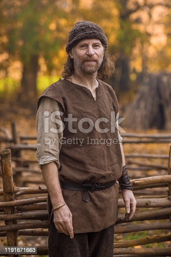 An individual viking man posing for an individual pic in a viking settlement village setting