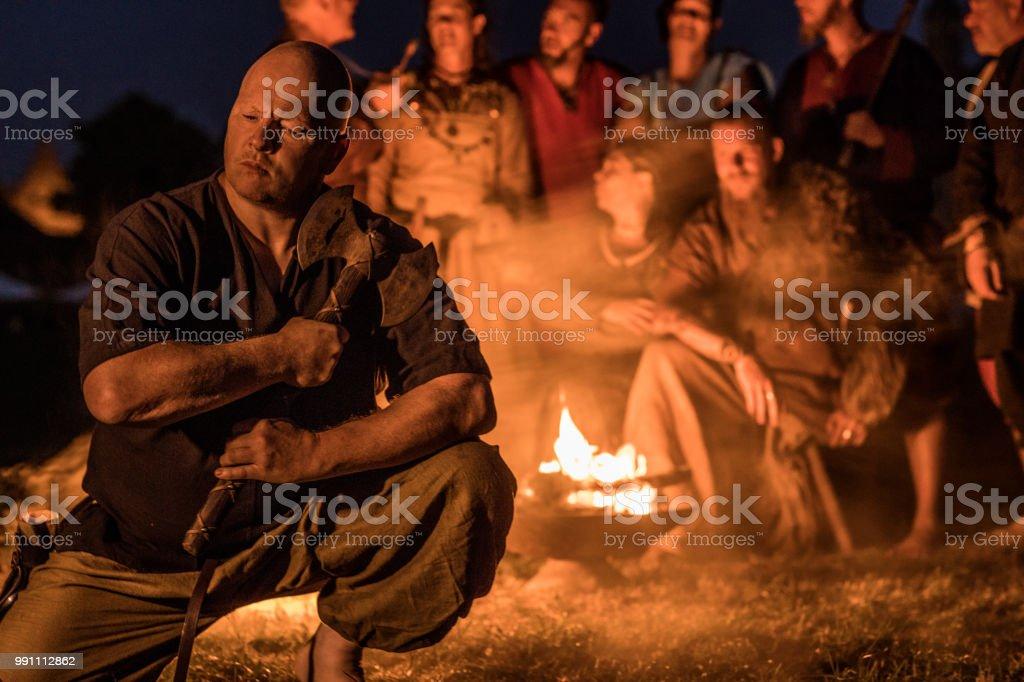 Um viking individual sentado na frente de um grupo de guerreiros ao redor de uma fogueira à noite - foto de acervo