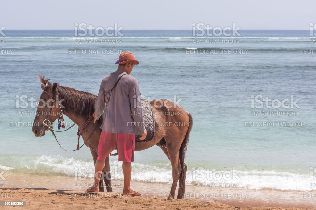 An indonesian man and his horse standing alone on the beach - Royalty-free Adult Stock Photo