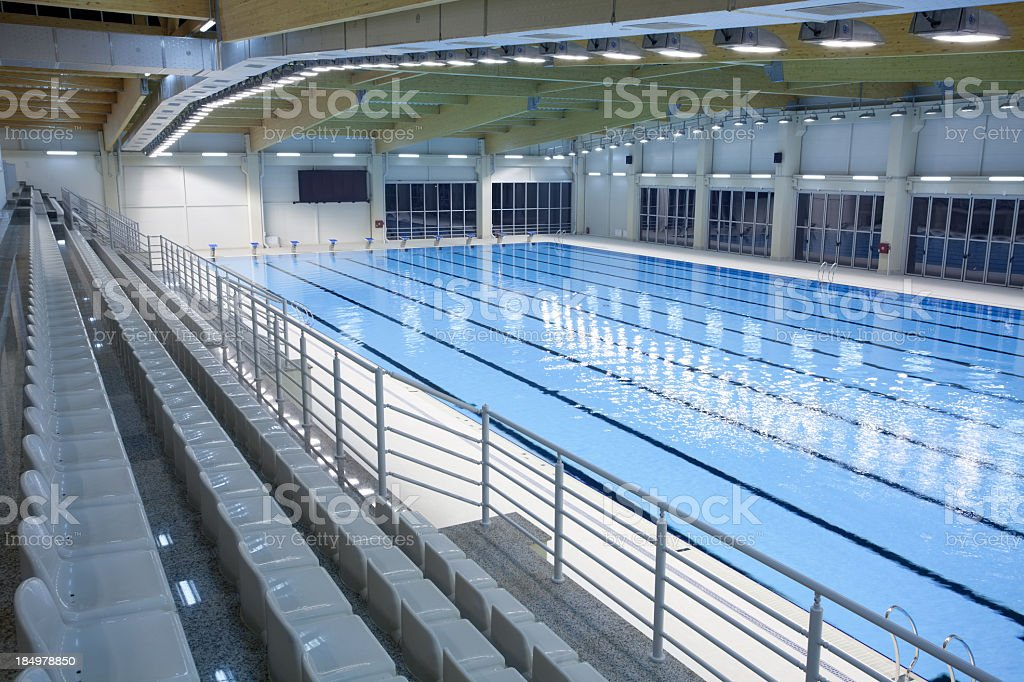 An indoor swimming pool with empty spectator seats stock photo