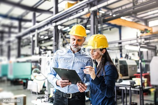 A portrait of an industrial man and woman engineers in a factory checking documents.