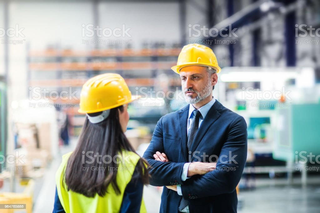 An industrial man and woman engineers in a factory talking. royalty-free stock photo