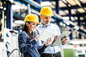 A portrait of an industrial man and woman engineers standing in a factory, talking.