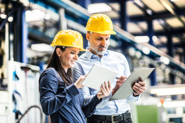 An industrial man and woman engineers standing in a factory using tablet. stock photo