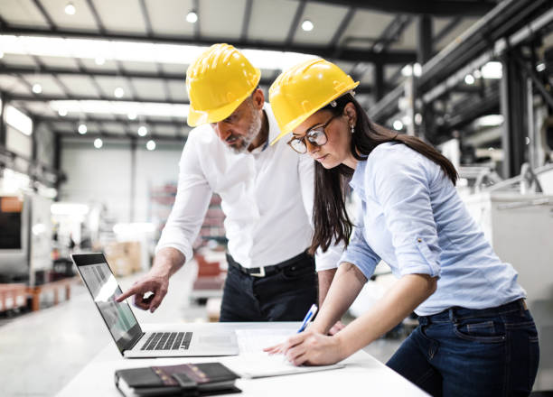 An industrial man and woman engineers with laptop in a factory checking documents. stock photo