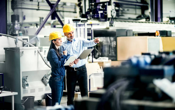 An industrial man and woman engineers with tablet and clipboard in a factory, discussing issues. stock photo