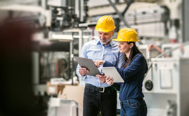 An industrial man and woman engineers with tablet in a factory checking documents. stock photo