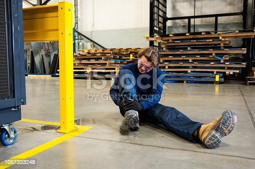 An industrial, manufacturing, safety topic. A worker in pain after slipping on liquid in an industrial plant.