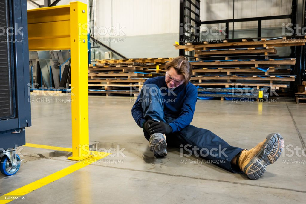 An industrial, manufacturing, safety topic.  A worker in pain after slipping on liquid in an industrial plant stock photo