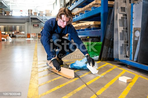 An industrial safety topic.  A worker picks-up trash from the floor in a manufacturing plant.  Housekeeping issues are major contributors to safety incidents.