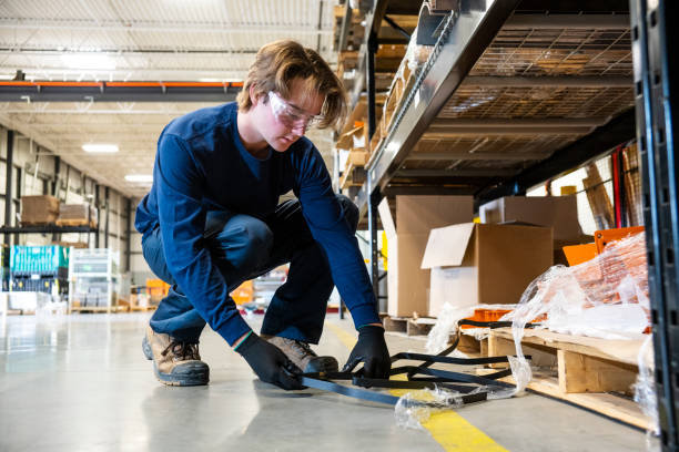 An industrial safety topic.  A worker picks-up trash from the floor in a manufacturing plant. stock photo