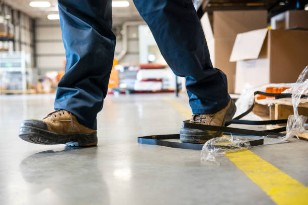 An industrial safety topic.  A worker tripping over a trash on a factory floor stock photo