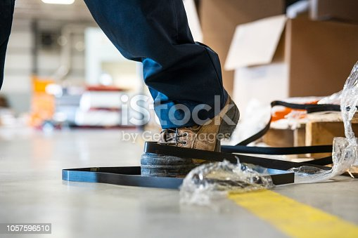 An industrial safety topic.  A worker in danger of tripping over a piece of metal strapping in a factory.